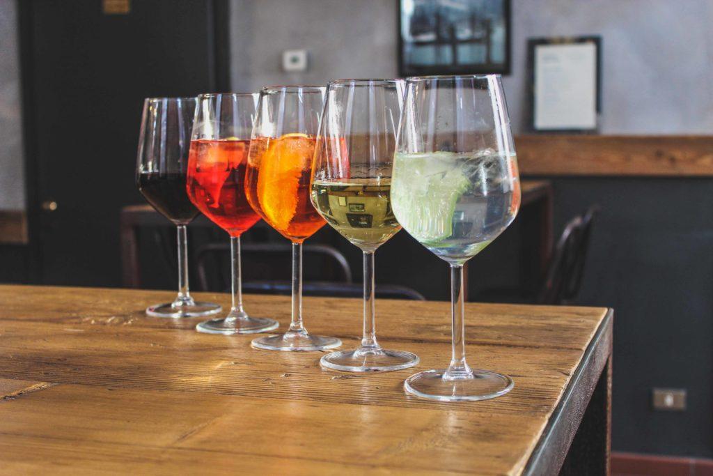 cinque bicchieri con aperitivo su un tavolo di legno vintage