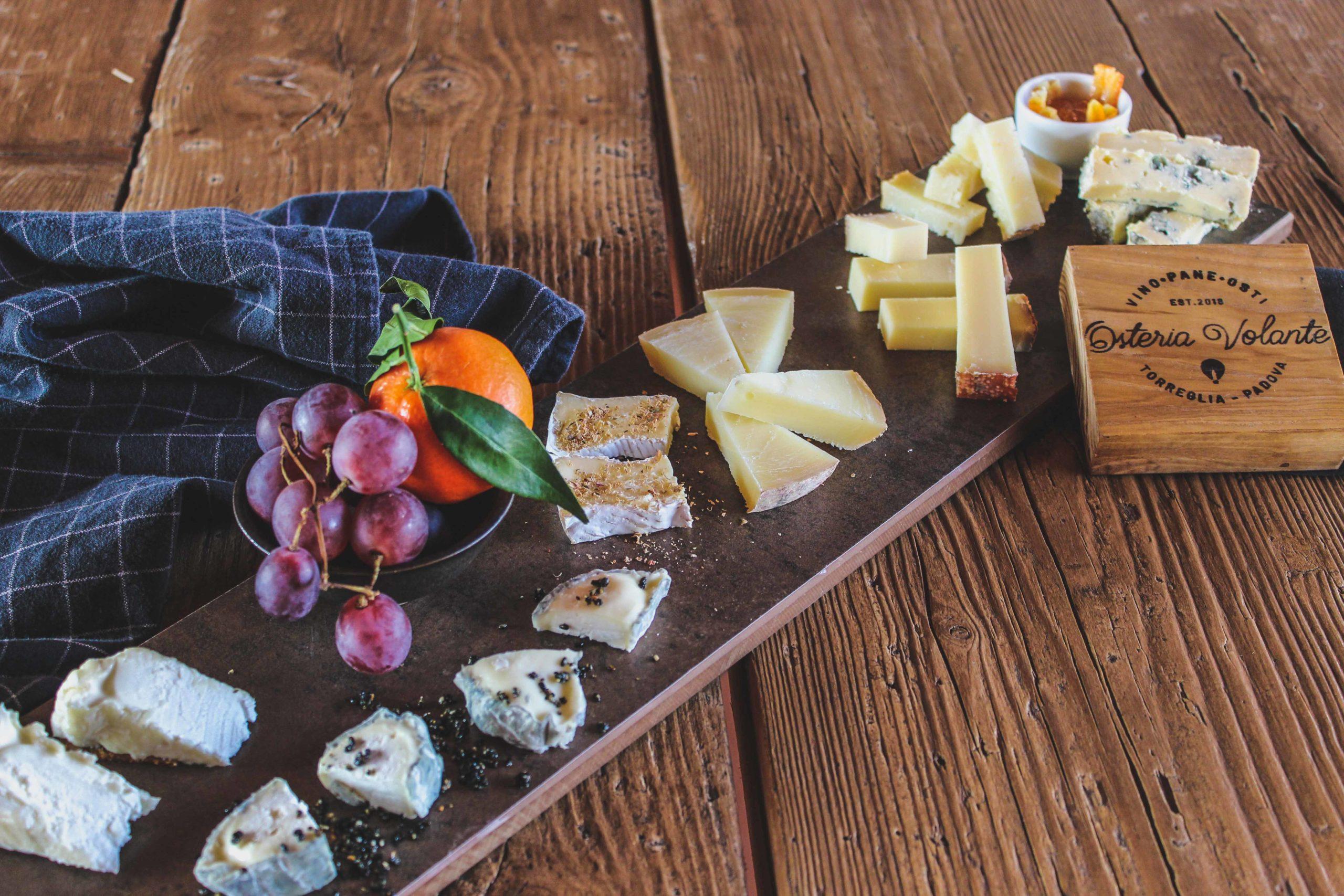 formaggi misti su un tagliere con uva e mandarini