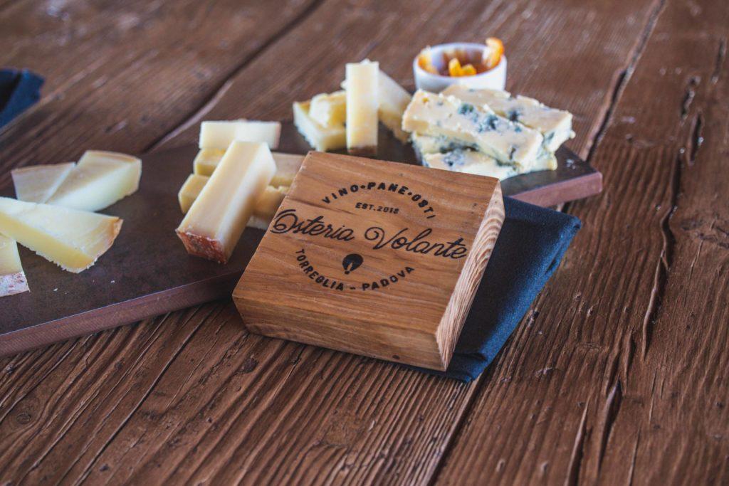 osteria forma di legno con logo e tagliere di formaggi misti