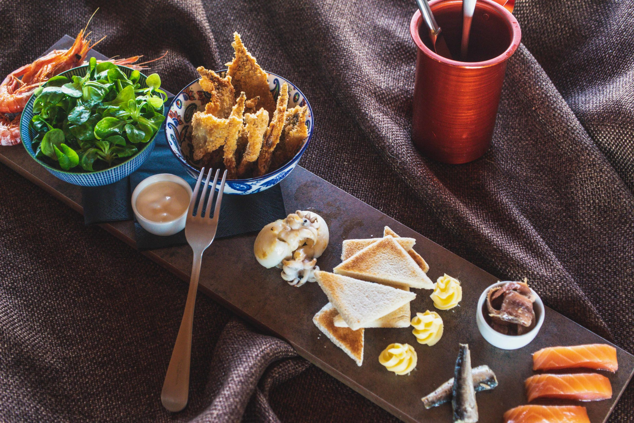 tagliere con pesce, pane tostato, insalata e salse