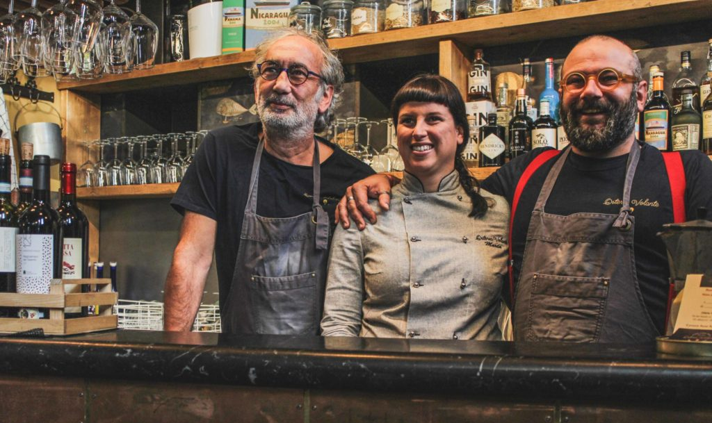 tre osti sorridenti al bancone bar storia